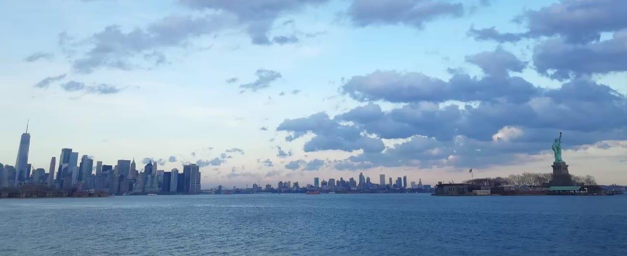 湖の向こうにある都市のビルと自由の女神
